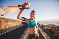 Geeignete junge Frau hoch, ihren Freund nach einem Lauf fiving lizenzfreie stockfotografie