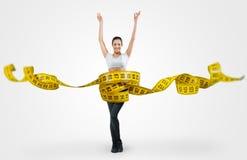 Geeignete junge Frau mit einem großen messenden Band Stockfotos