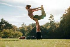 Geeignete junge Paare, die acro Yoga tun Stockfotografie