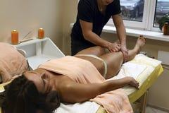 Geeignete Klientin des Brunette, die vorbei Körpermassage am Badekurortclub empfängt Lizenzfreie Stockfotos