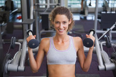 Geeignete lächelnde Frau, welche die Gewichtsmaschine für ihre Arme verwendet Lizenzfreies Stockbild