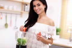 Geeignete lächelnde junge Frau, die gesunden Smoothie in der modernen Küche zubereitet Lizenzfreie Stockbilder