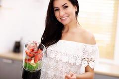 Geeignete lächelnde junge Frau, die gesunden Smoothie in der modernen Küche zubereitet Stockfotografie