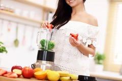 Geeignete lächelnde junge Frau, die gesunden Smoothie in der modernen Küche zubereitet Lizenzfreies Stockbild