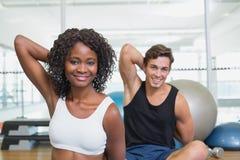 Geeignete Paare, die auf Übungsmatten aufwärmen Stockbilder