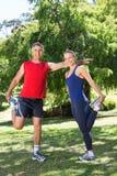 Geeignete Paare, die in den Park ausdehnen Lizenzfreie Stockbilder