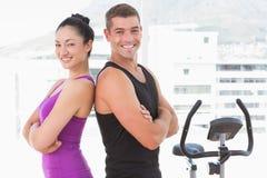 Geeignete Paare, die an der Kamera mit den Armen gekreuzt lächeln Stockbilder