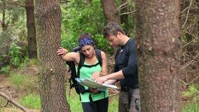 Geeignete Paare, die eine Waldfläche liest eine Karte erforschen stock video