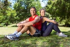 Geeignete Paare, die im Park sitzen Lizenzfreie Stockfotos