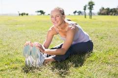 Geeignete reife Frau, die auf dem Gras aufwärmt Lizenzfreie Stockfotografie
