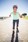 Geeignete reife Frau, die auf dem Pier rollerblading ist Lizenzfreie Stockfotografie