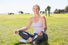 Geeignete reife Frau, die in der Lotoshaltung auf dem Gras sitzt Stockfoto