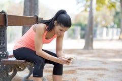 Geeignete Sportfrau, die Spurhaltungsleistung Handyinternet-APP nach dem laufenden Training sitzt auf der Parkbank glücklich betr lizenzfreie stockfotografie