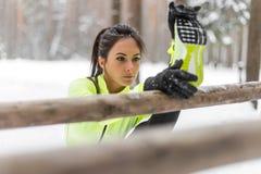 Geeignete Sportlerin, die das Kniesehnenbein draußen ausdehnt Übungen in Holz tut Vorbildlicher trainierender Winterpark des weib Lizenzfreies Stockfoto