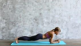 Geeignete sportliche Frau, die eine Planke auf Yogamatte tut stock footage