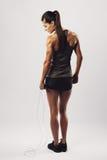 Geeignete und muskulöse Frau mit springendem Seil stockfoto