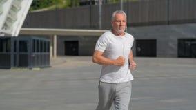 Geeigneter älterer Mann, der in die Stadt läuft