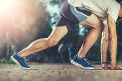 Geeigneter Athlet, der vor Rennen ausdehnt lizenzfreie stockfotos