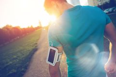 Geeigneter Athlet mit Armbinde gehend entlang die Straße im Park Stockbilder