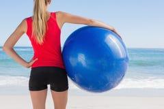 Geeigneter blonder haltener Übungsball, der Meer betrachtet Lizenzfreie Stockbilder