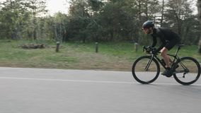 Geeigneter d?nner Berufsradfahrer, der ein schnelles und starkes Radeln des Fahrrades aus dem Sattel im Park heraus reitet Langsa stock video