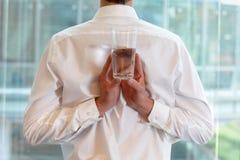 Geeigneter flexibler Geschäftsmann mit Glas Wasser stockfoto