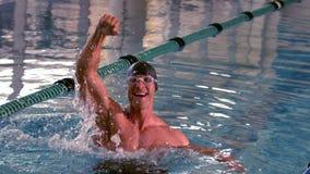 Geeigneter glücklicher Schwimmer, der oben springt und im Pool zujubelt stock video