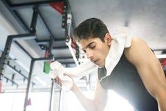 Geeigneter hispanischer Mann der Junge, beim Turnhallenabwischen schwitzte weg von seinem Gesicht Stockbilder