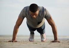 Geeigneter junger Mann, den das Handeln drückt, ups am Strand Stockfotos