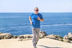 Geeigneter junger Mann, der auf einer laufenden Spur entlang Küste rüttelt Entspannender Eignungsathlet in der Sportkleidung Lizenzfreies Stockbild