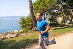 Geeigneter junger Mann, der auf einer laufenden Spur entlang Küste rüttelt Entspannender Eignungsathlet in der Sportkleidung geni Stockfoto