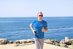 Geeigneter junger Mann, der auf einer laufenden Spur entlang Küste rüttelt Entspannender Eignungsathlet in der Sportkleidung geni Stockbild