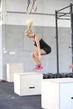 Geeigneter Kasten der jungen Frau, der an der Eignungsturnhalle springt Stockfoto