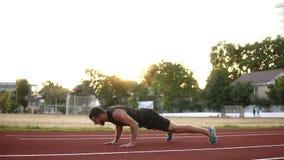 Geeigneter männlicher Boxer in crossfit Übung draußen, das aktive Trainieren tuend und drücken ups auf das Freienstadion in stock footage