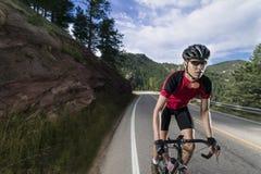 Geeigneter männlicher Radfahrer, der rote Trikotreitgebirgsstraße trägt stockfoto