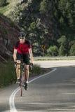 Geeigneter männlicher Radfahrer, der rote Trikotreitgebirgsstraße trägt stockfotografie