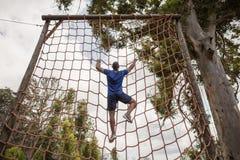 Geeigneter Mann, der ein Netz während des Hindernislaufs klettert lizenzfreie stockbilder