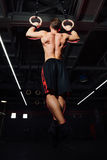 Geeigneter Mann der Junge, der auf gymnastischen Ringen hochzieht Lizenzfreie Stockfotos