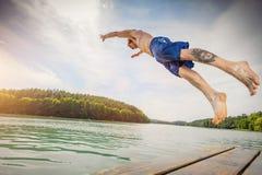 Geeigneter Mann der Junge, der in einen See springt Lizenzfreie Stockbilder