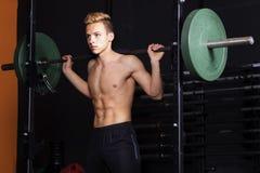 Geeigneter Mann der Junge mit Dummkopfgewichts-Ausbildungsanlageen auf Sportturnhalle Lizenzfreie Stockbilder