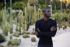 geeigneter Mann in der schwarzen aktiven Kleidung, die draußen Pause nach Lauf macht Stockbild