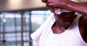 Geeigneter Mann, der seine Braue abwischt und an der Kamera lächelt stock footage
