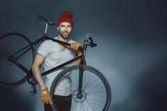 Geeigneter Mann des hübschen Sports, der Fahrrad hält Gut aussehender Mann mit bicycl stockfoto