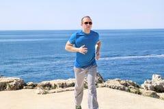 Geeigneter muskulöser Mann, der auf einer laufenden Spur entlang Küste rüttelt Entspannender Eignungsathlet in der Sportkleidung  Lizenzfreies Stockbild