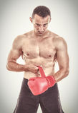 Geeigneter muskulöser Mann, der seine Boxhandschuhe vor Kamera setzt Stockbild