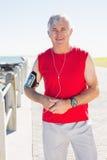 Geeigneter reifer Mann, der an der Kamera auf dem Pier lächelt Lizenzfreies Stockbild