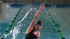 Geeigneter Schwimmer, der im Swimmingpool springt und zujubelt