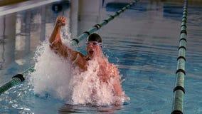 Geeigneter Schwimmer, der oben springt und im Pool zujubelt stock footage