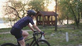 Geeigneter sportiver weiblicher Radfahrer auf einem Fahrrad im Stadtpark vor Sonnenuntergang Radfahrenkonzept Langsame Bewegung
