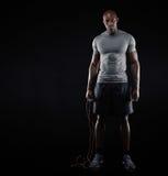 Geeigneter und muskulöser Mann mit springendem Seil Stockbild